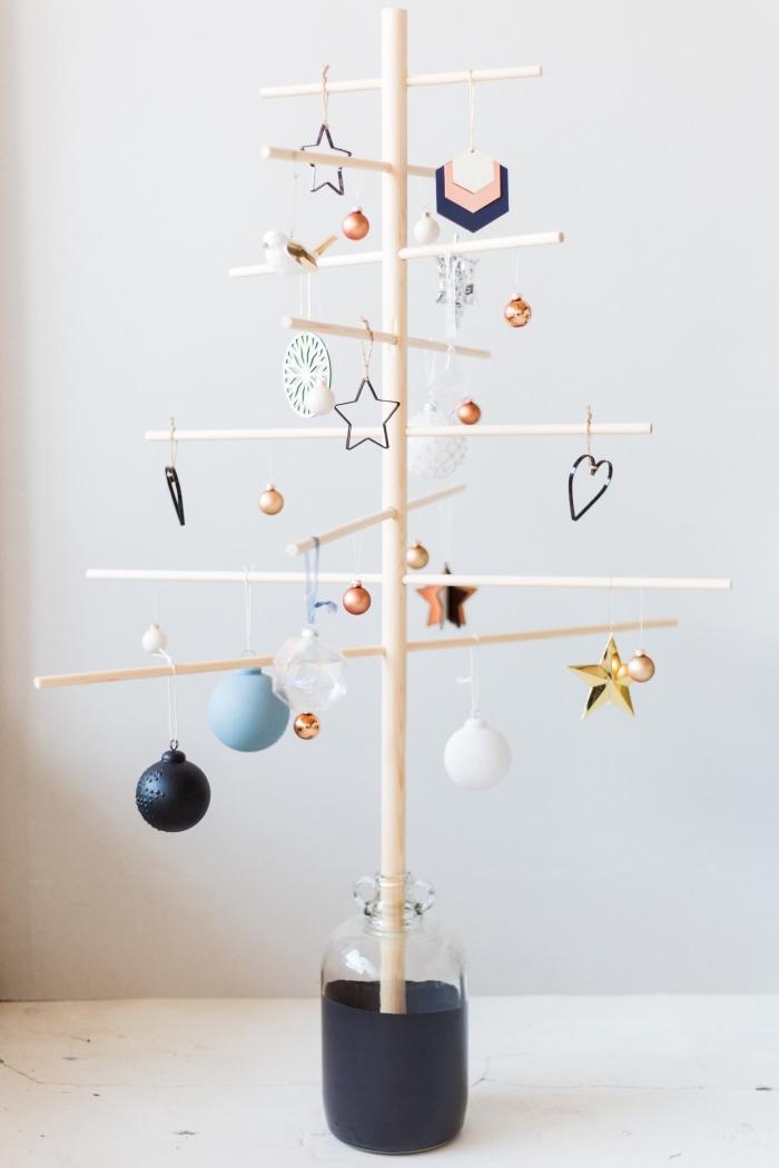 modèle original et minimaliste d'un sapin de noel en bois, un support en bois naturel posé dans un vase demi transparent en verre et décoré de multitude de suspensions de noel