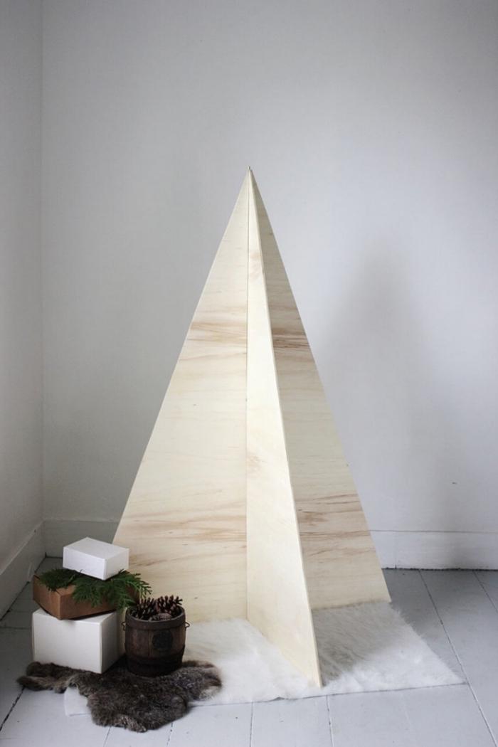 sapin de noel en bois au design minimaliste, fait avec des planches en bois clair, pour une déco de fête de style scandinave, sapin décoratif en bois posé sur un tapis cocooning blanc