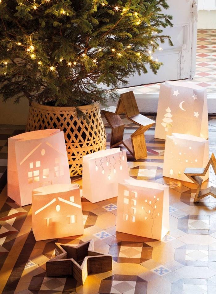 decoration de noel fait main avec des pochettes en papier découpées à bougies led posés au sol autour du sapin