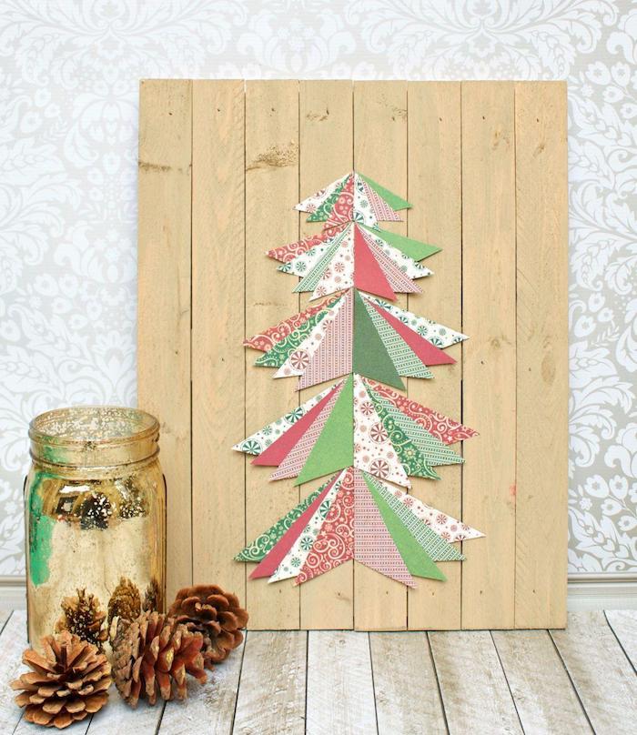 sapin de noel sur panneau en lattes de bois avec sapin de noel en triangles papier colorés, bocal en verre couleur or et pommes de pin
