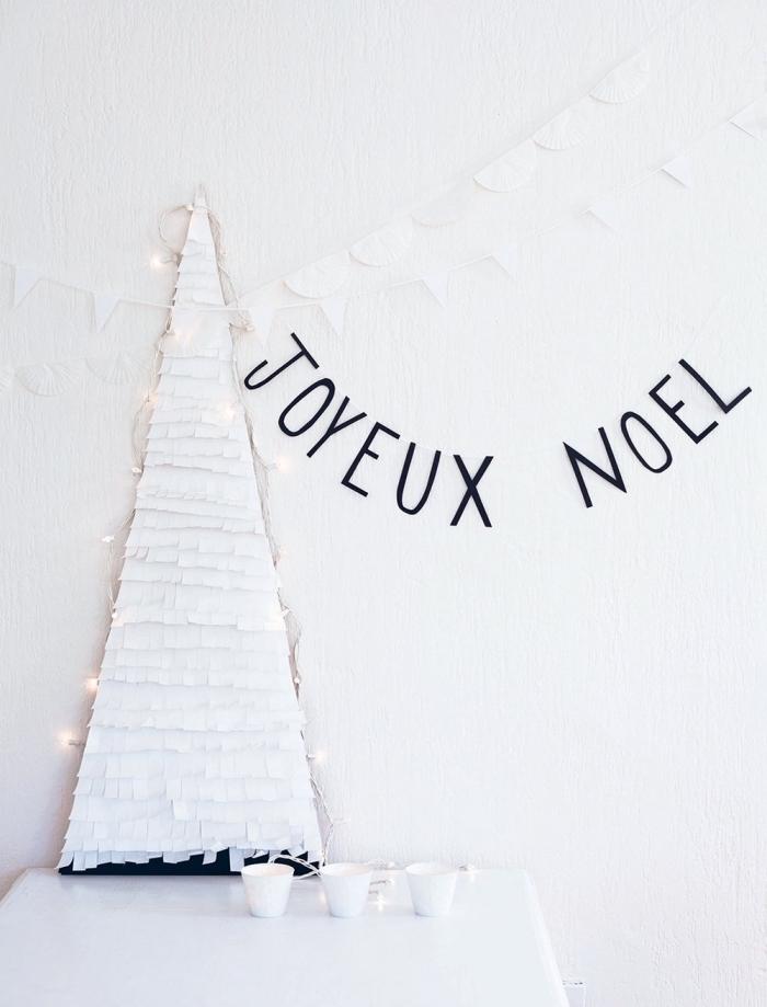 petit sapin de noel en papier réalisé à partir d'une base en carton recouvert de papier blanc frangé et posé sur table, appuyé au mur