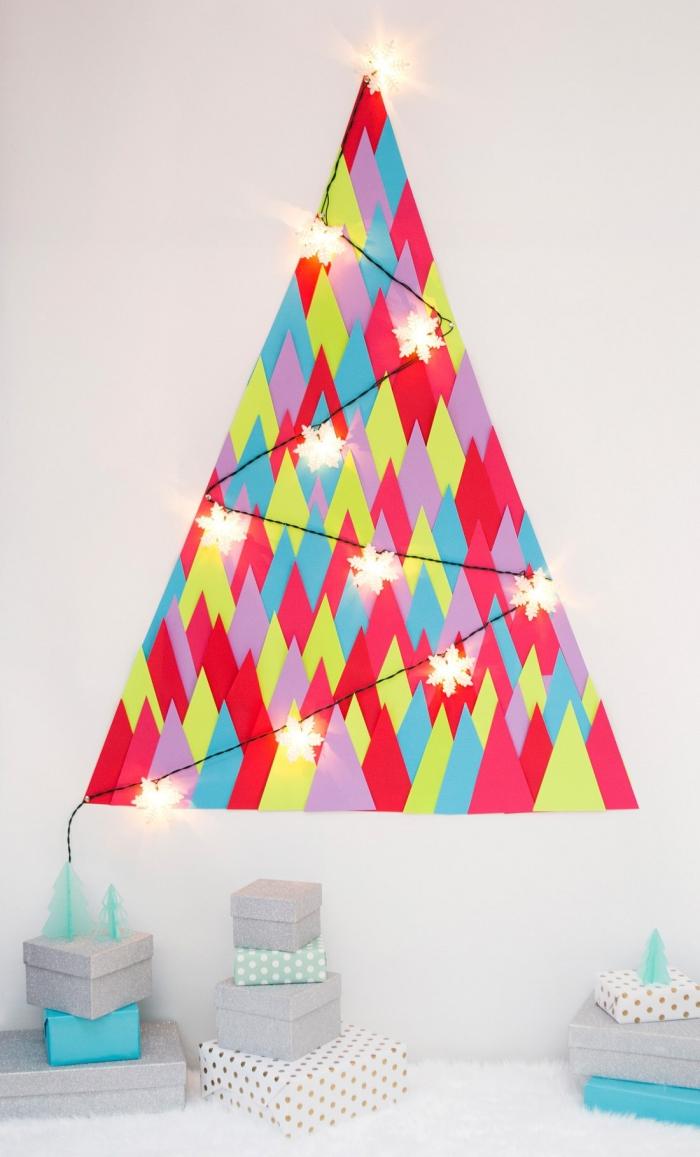 sapin de noel mural réalisé à partir de triangles en papier de couleurs différentes, orné d'une jolie guirlande lumineuse, decoration de noël à fabriquer en papier pour une petite chambre