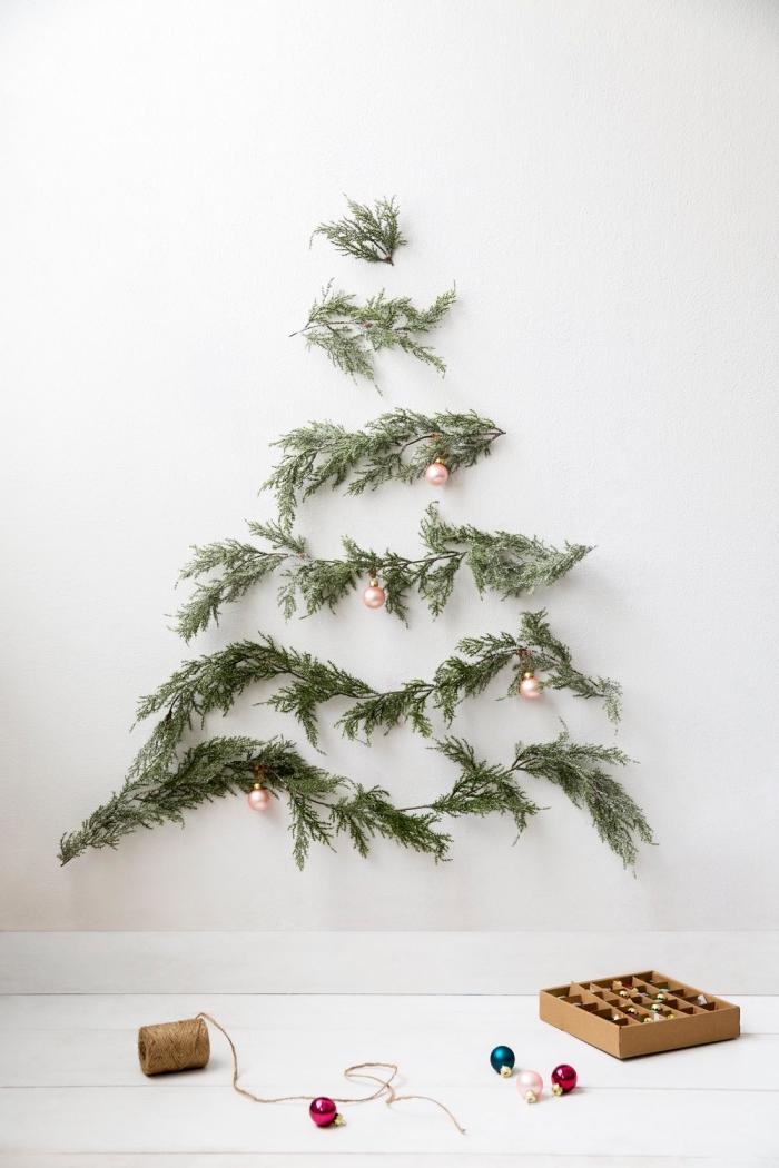 idée deco sapin de noel minimaliste et gain de place, des branches de sapin posées au mur pour former la forme d'un arbre de noël, décorées de quelques petites boules de noël