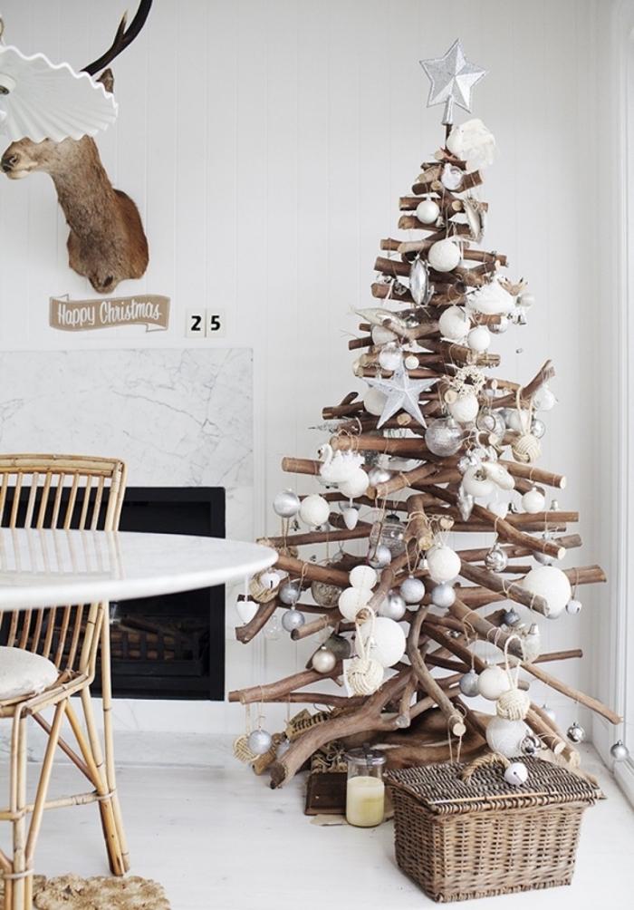 sapin de noel en bois de style rustique et naturel, fait avec des branches et orné de boules de noël blanc et argent qui s'harmonise avec l'intérieur épuré du salon