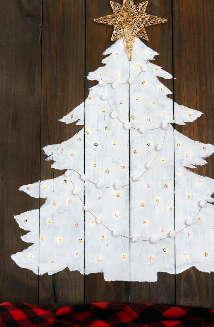 image sapin de noel, arbre de noel peint sur une palette, étoile en fil doré, guirlande de pompons, petites lampes insérées