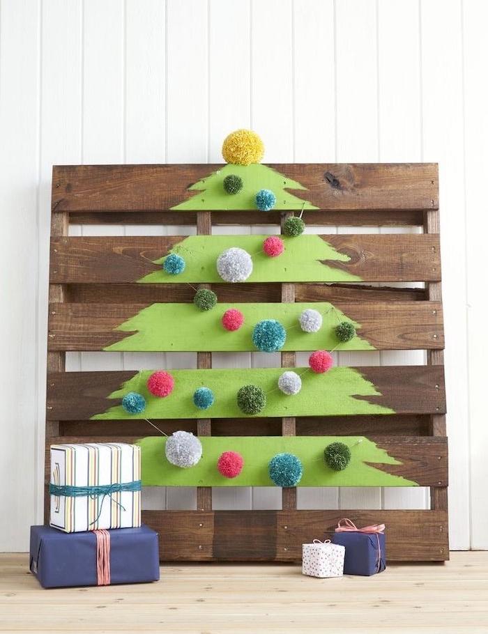 fabriquer sapin de noel en palette de bois avec dessin sapin vert décoré de pompons colorés, cadeaux rangés autour