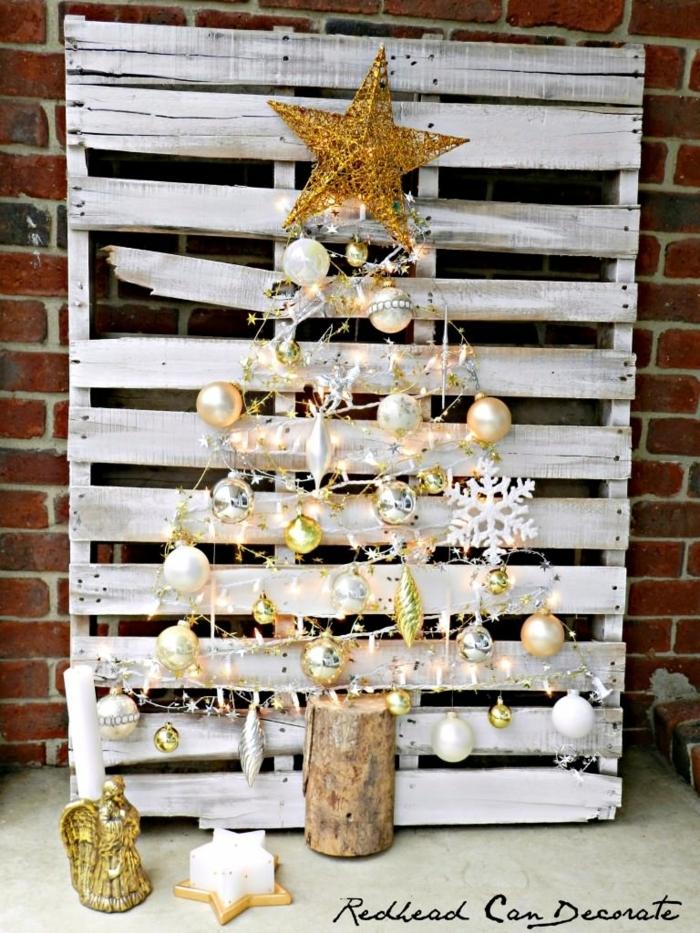 palette blanche avec décoration féerique, tronc de bois, grande étoile jaune, boules dorées et argentées, mur en briques