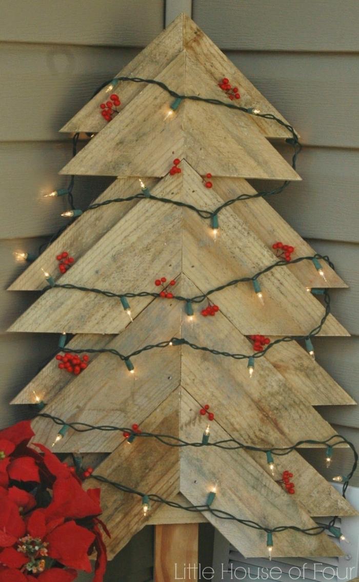 sapin en morceaux de bois coupé, guirlande verte, ampoules électriques, baies rouges, plante fleurie en papier