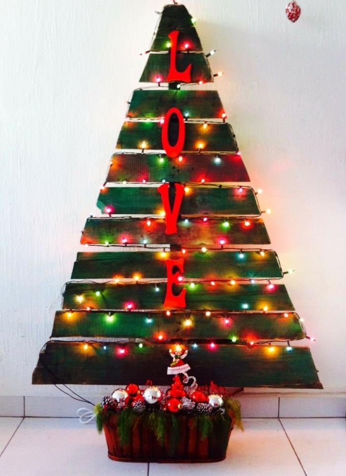 arbre de noel chaleureux aux ampoules colorées, jouets de noel empilés et verdure, grandes lettres décoratives, sapin en palettes