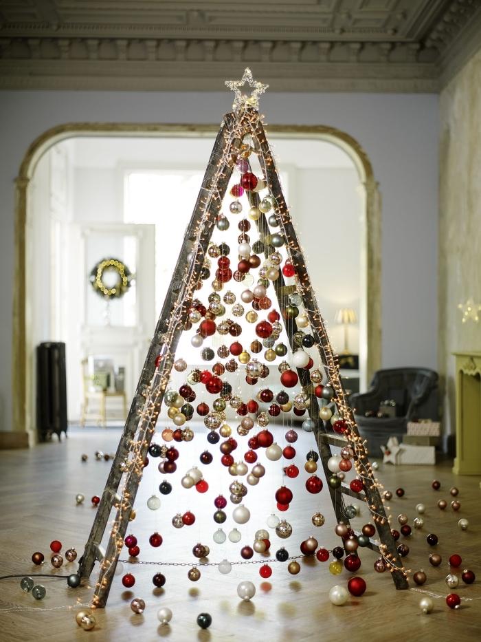 une échelle en bois transformée en sapin de noël original recouvert de boules de noël en or, blanc et rouge, avec une jolie étoile déposée en haut