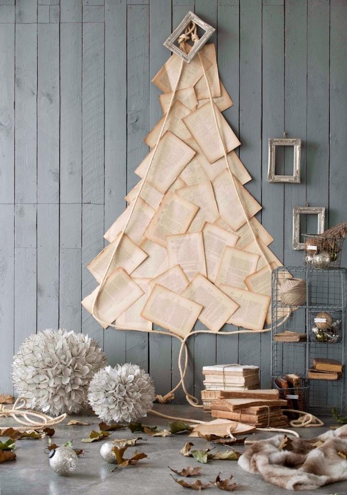 idée deco sapin de noël insolite réalisé avec des pages de livre ancien collées au mur en forme d'arbre, déco de noël vintage avec du papier et des cadres anciens sur un fond de bois gris