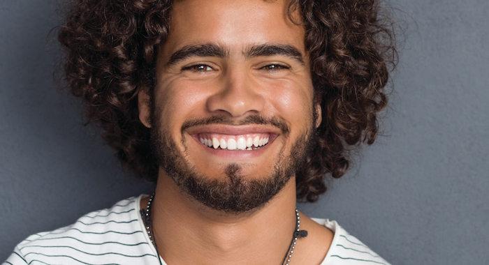 idée cheveux bouclés homme mi long avec sourire dents blanches et barbe courte style brésilien