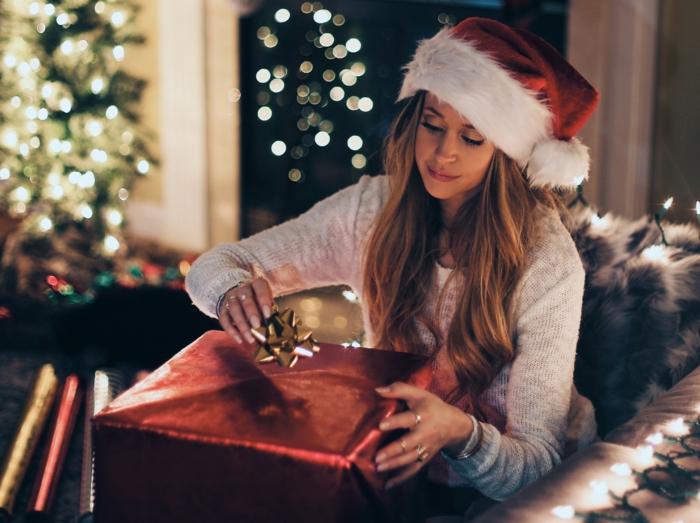 Recevoir un cadeau, femme jolie avec chapeau de père noel, porter un pull blanc et des jeans pour la fete de noel