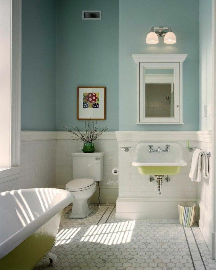 mur bleu, tomettes blanches, baignoire blanc et vert, placard avec miroir, lavabo vintage en résine en blanc et vert, cadre peinture