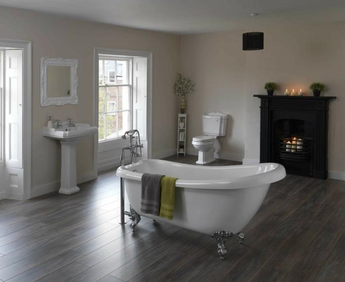 salle de bain spacieuse avec le sol en bois, baignoire centrale asymétrique, lavabo colonne, cheminée avec bougies