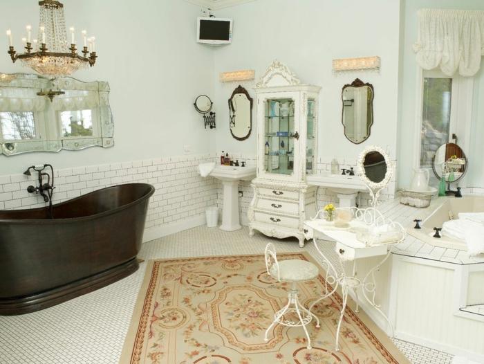 grande baignoire noire, grand chandelier victorien, miroir décoratif, tapis beige, petit tabouret et table blanche, deux lavabos, buffet vintage