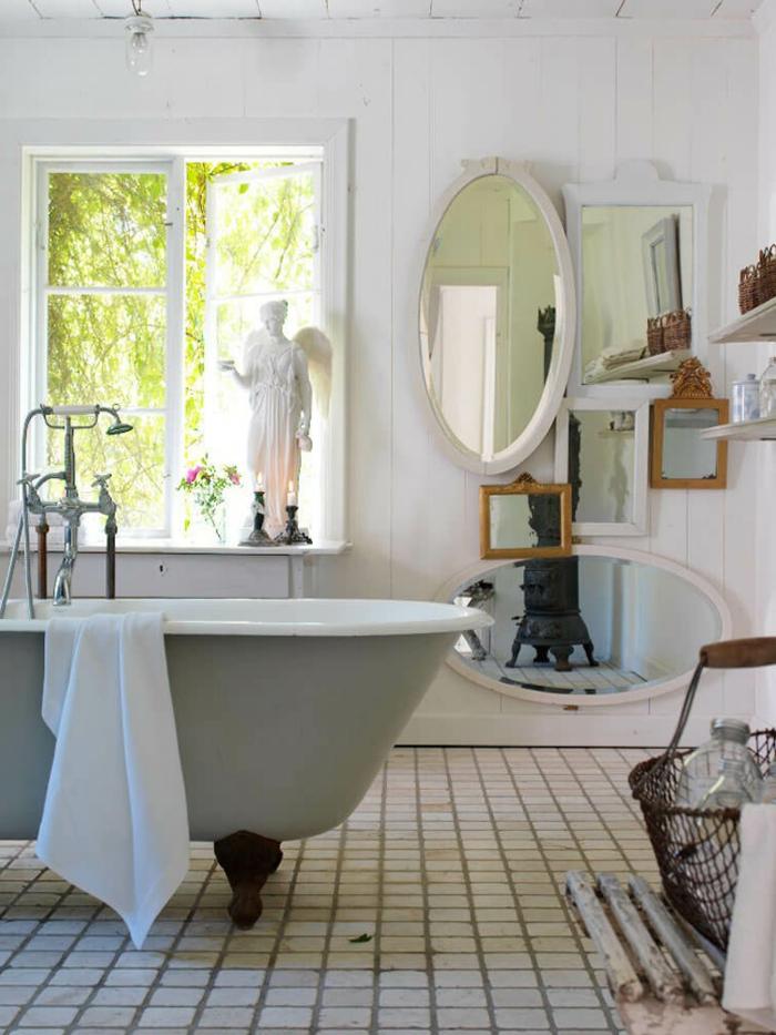 salle de bain antique, miroir ovale blanc, grande baignoire centrale, sol carreaux blancs, poêle rustique, lambris blanc