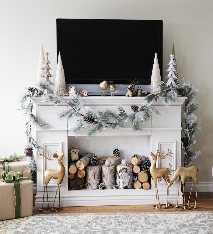 fausse cheminée comme support tv avec décoration de noel guirlande de pin et buches de bois dans foyer dans une déco scandinave