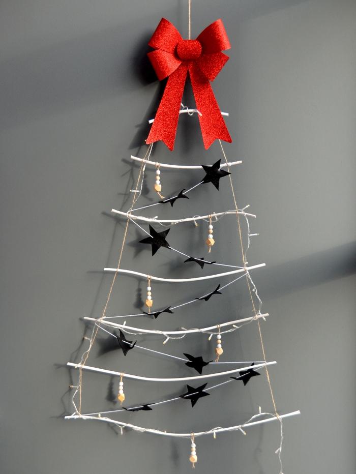 un sapin échelle à suspendre réalisé avec des branches de bois très fines, décoré avec des ornements minimalistes en papier et en perles de bois, sublimé par un joli noeud rouge