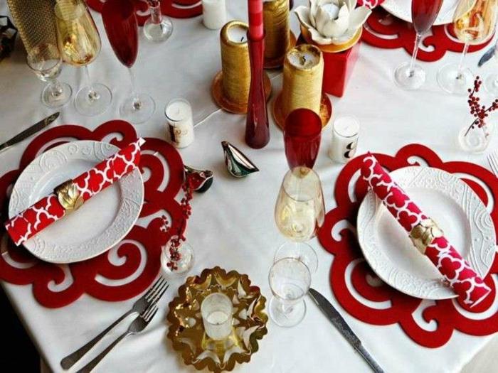 table de f te sous assiettes rouges motifs d coup s porte bougie dor  serviettes baroques en rouge et banc bougies dor es et rouges nappe blanche deco de table noel