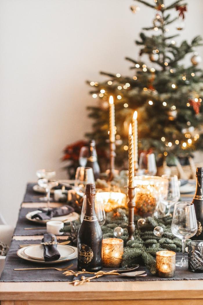 table en bois chemin de table noir branches de pin porte bougies hautes bouteille de champagne sapin de noel d cor  ustensiles dor es