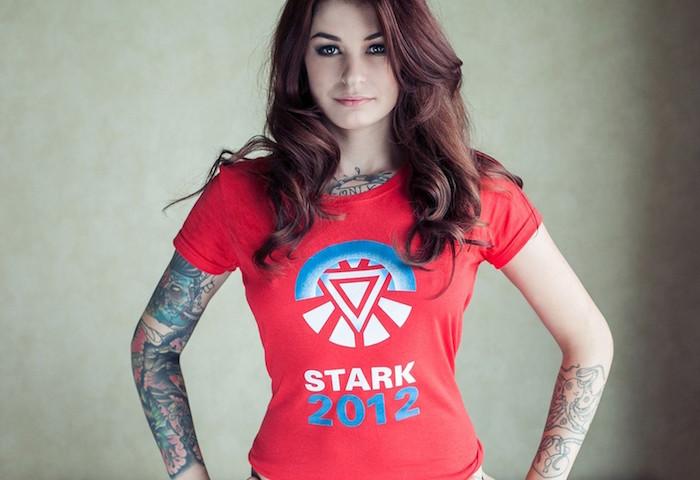 femme avec bras couvert de tatouages en couleurs et ligne noire avec tee shirt stark