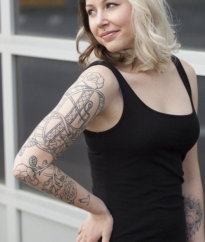 photo tatouage bras complet en ligne noire avec fleurs roses et manege grand huit pur femme blonde