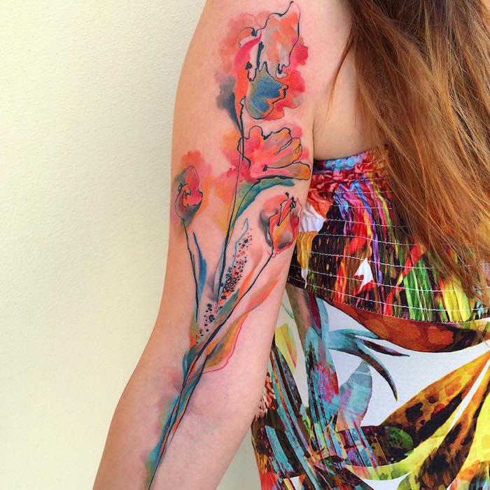 tatouage fleur abstraite en couleurs aquarelle watercolor sur bras de femme avec robe colorée