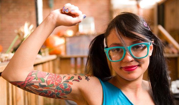 femme brune avec tatouages de bonbons et sucettes candy sur le le bras en couleurs retro
