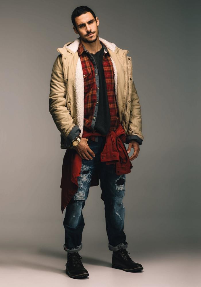 superposition de pièces pour un look d'hiver pratique inspiré de la mode ouvrière, blouson homme d'hiver à doublure imitation peau lainée porté en dessus d'une veste en jean et d'une chemise flanelle à carreaux