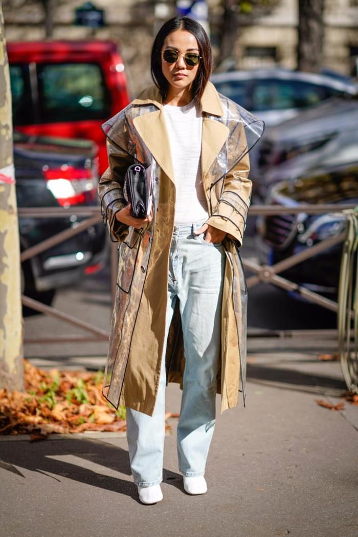 manteau tendance femme, coupe vent long vinyl, jeans bleus, lunettes de soleil rondes
