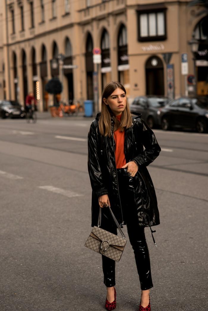 cuir stretch femme, sac tendance, pull orange, veste vinyl noire, jeune femme, boulevard, joli bâtiment