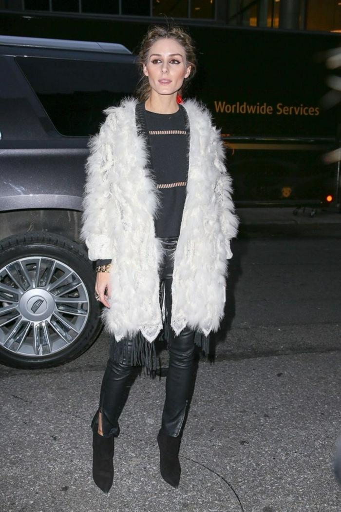 Olivia Palermo avec pantalon en cuir et pull noir, manteau poil long blanc, bottines noires