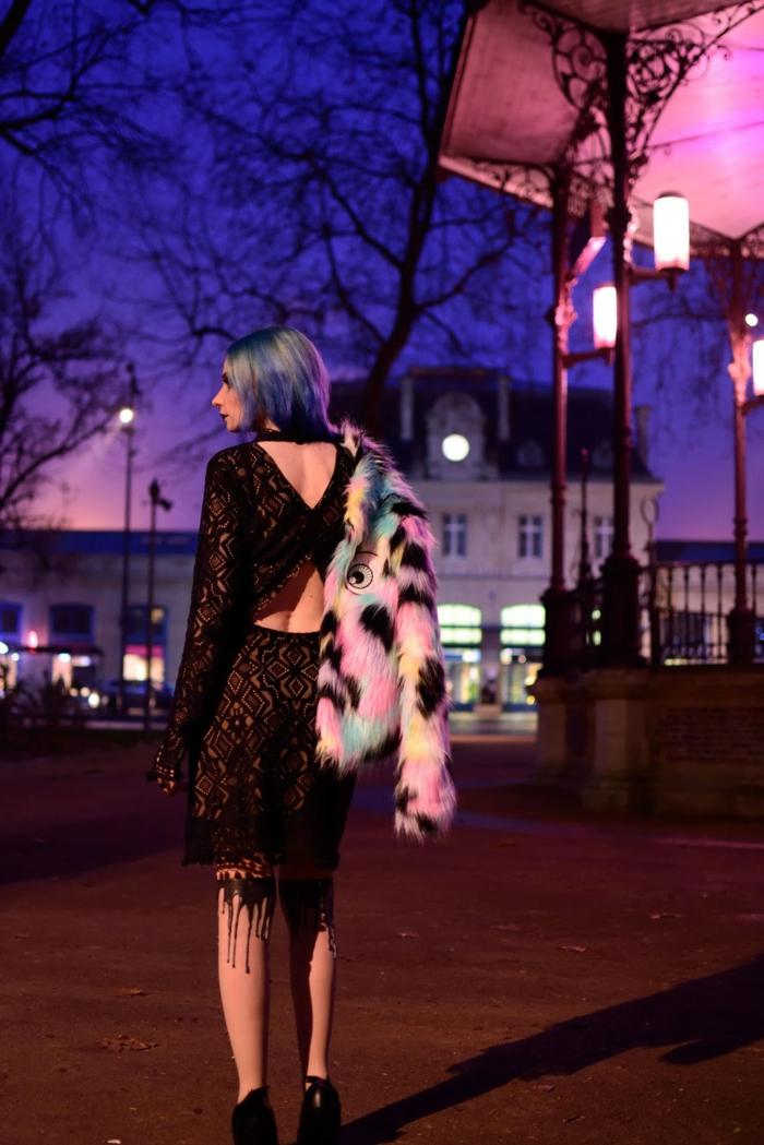jeune femme en robe noire, manteau fourrure original, chaussettes fines originales, cheveux bleus, tenue de fête gothique