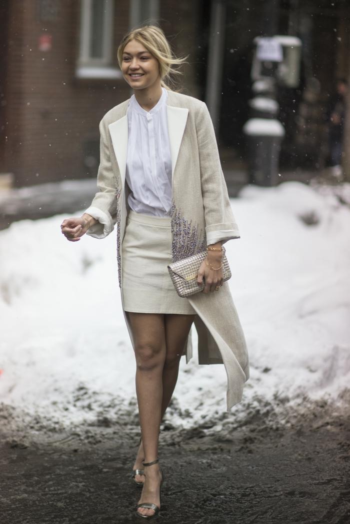 manteau gris clair, jupe moulante courte, sac enveloppe métallique, chemise blanc sandales élégantes