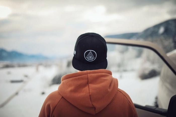 mode masculine, casquette noire, sweat à capuche couleur terracotta, homme qui voyage en hiver avec sa voiture