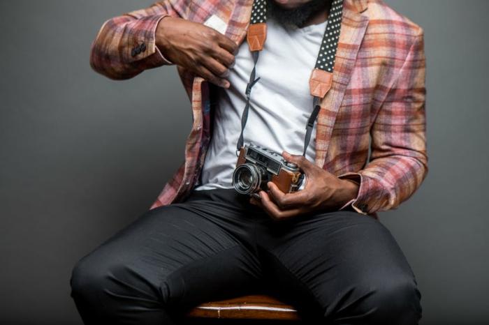 tenue d'homme moderne, chemise carreaux tissu épais, tee-shirt blanc, pantalon gris foncé, appareil photo
