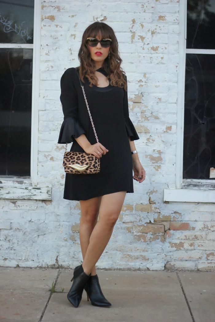 robe courte noire, manches à volants, bottines noires, sac imprimé géométrique, lunettes de soleil, mur en broques blanches