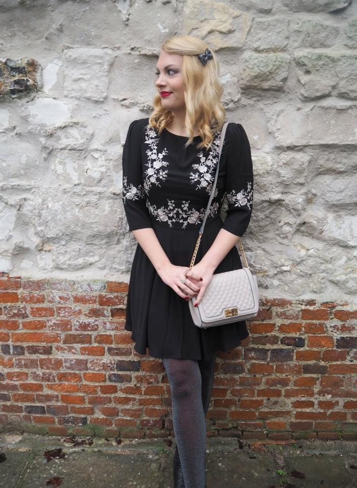 tenue de femme style boho, barette de cheveux papillon noir, robe aux motifs floraux jupe plissée, sac matelassé blanc