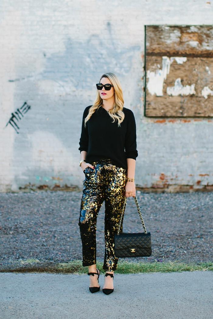 pantalon glamour style nouvel an, pull noir, sac matelassé, lunettes de soleil, cheveux bouclés