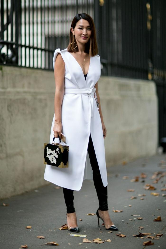 manteau long sans manches, pantalon noir, sac boîte aux éléments floraux, escarpins bicolores