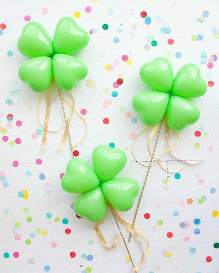 trois trèfles vertes en ballons verts en forme de coeurs, confettis colorés, ruban doré