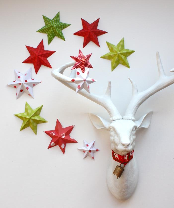 des étoiles 3d en papier origami fixées au mur autour d'une trophée de cerf blanche, deco de noel maison