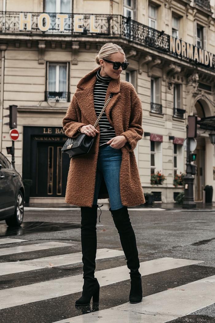 manteau teddy, bottes longues, jeans bleus, blouse aux rayures, joli bâtiment moderne, mode femme chic