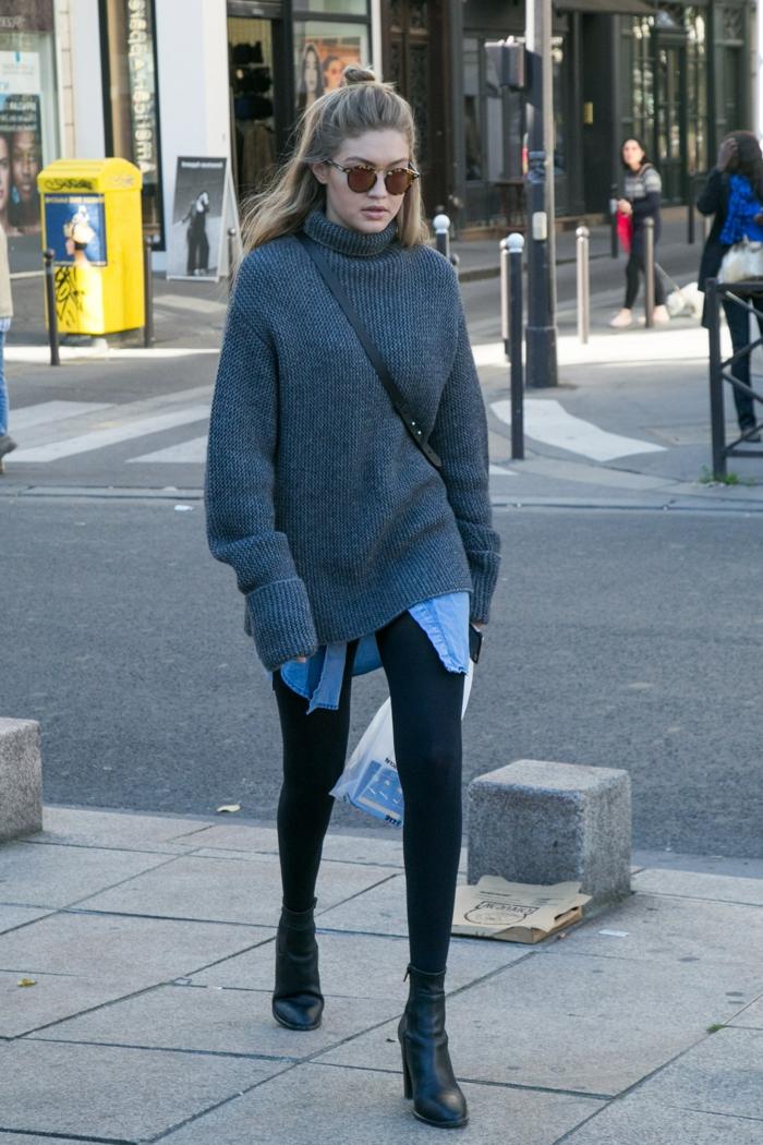 pull oversize. Gigi Hadid, chemise longue denim, coiffure demi bun, leggings noirs, bottines noires, lunettes de soleil rondes