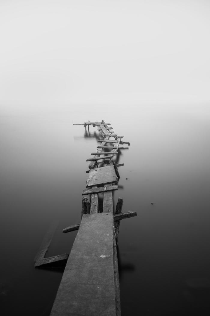 image noir et blanc d'ancien quai en bois entouré des eaux calmes de la mer
