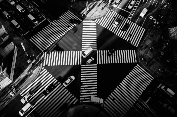 photo noir et blanc d'un grand croisement à tokyo vu d'en haut avec ses lignes blanches du marquage au sol, photographie de paysage urbain