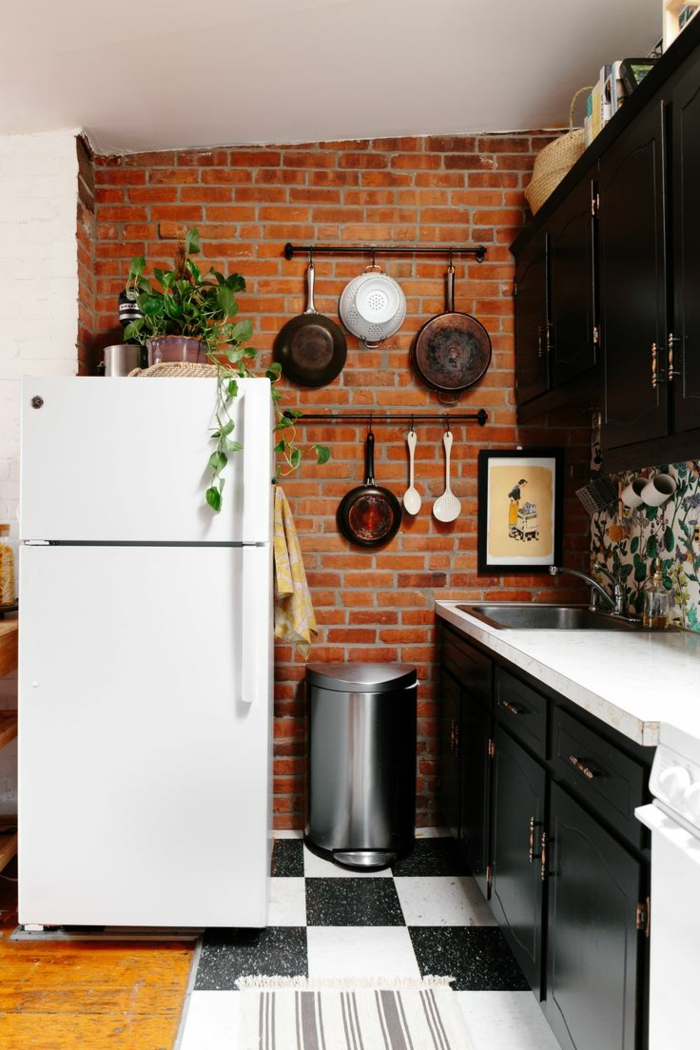 mur en briques, ustensiles suspendus, frigo blanc, armoires de cuisine noires, carrelage damier, amenagement cuisine originale