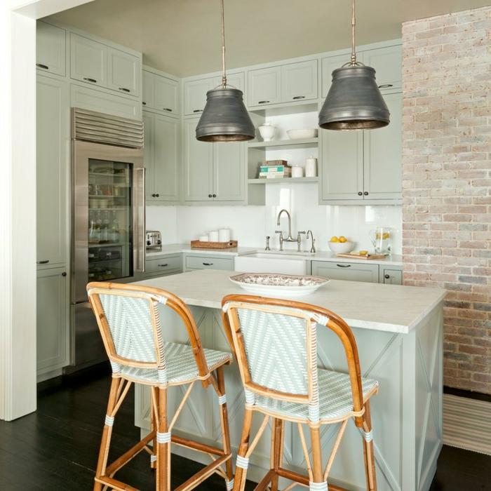 armoires de cuisine, frigo encastrable, mur en briques, lampes suspendues industrielles, évier blanc au robinet rétro