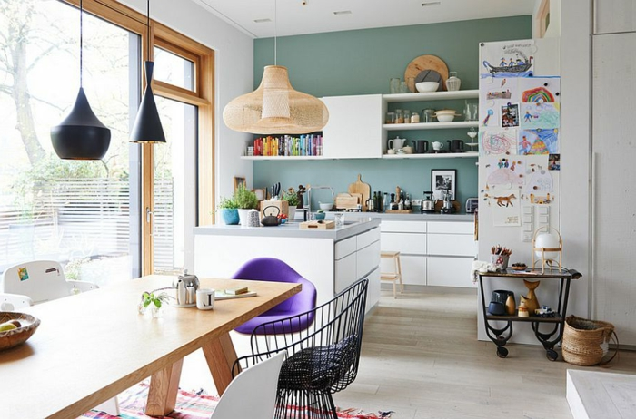 petite cuisine et salle à manger, grande table à manger en bois, suspensions tom dixon, grandes fenêtres à l'encadrement bois, étagères murales blanches